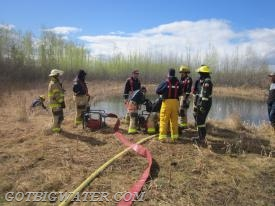 Folks work through testing the flows of various portable pumps and determining the best set-up arrangement.  A dugout (pond) at the HLFD training center was used as the supply source.