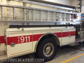"On a ""city"" pumper, we probably would find standpipe racks where the tray is located. On this ""rural"" pumper, we find a length of suction hose. Both items are just as important in their own locality."