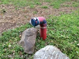 This dry fire hydrant is located near a river and has plenty of access to good, clean water.