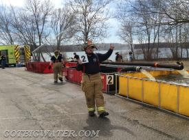 "This firefighter using handheld ""flip"" signs directs tankers to the ""correct"" dump tank....meaning the one in which the Dump Site Officer wants the water dumped. While this position does require another human being, on large scale ( 4 or more dump tanks) operations this position can really help keep things running smoothly."