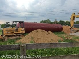 The tank is delivered and stored on site while the hole is dug.