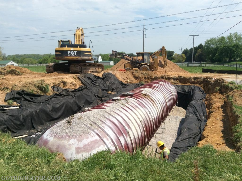 The tank is in the ground and strapped down to the concrete base. Gravel is now being used as backfill around the tank.