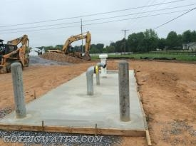 Protective concerete-filled, steel pipe bollards are installed at the end of the concrete pad to protect the tank fittings from vehicles.