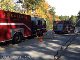 The first arriving pumper (right) initiates water flow while the second arriving pumper supplies additional tank water.